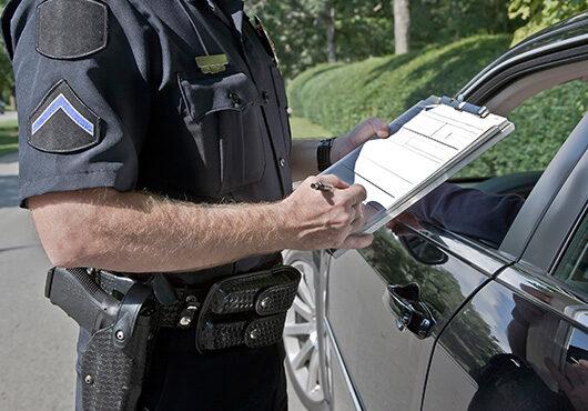 An officer writing a speeding ticket