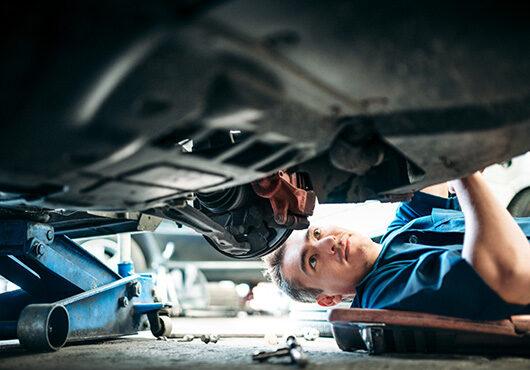 Car Mechanic Working Under Vehicle