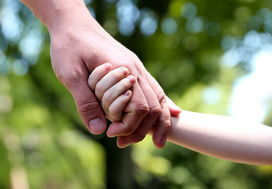 Father holds the hand of a small child