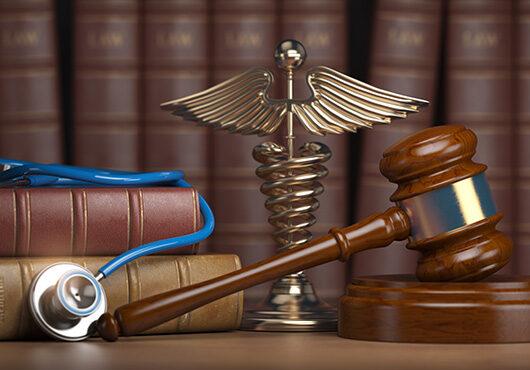 Gavel, stethoscope and caduceus sign on books background