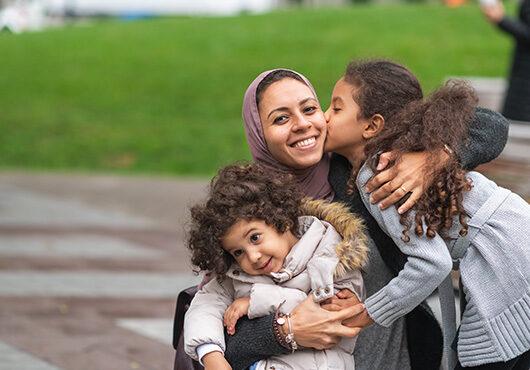 Muslim mother hugging daughters in city park