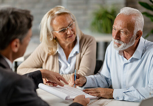 Senior couple signing a contract while having a meeting with insurance agent