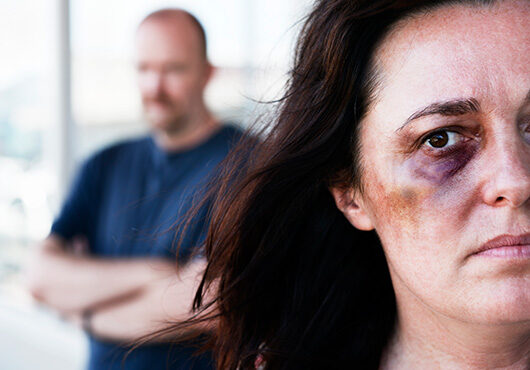 Victim of domestic violence with threatening man in background